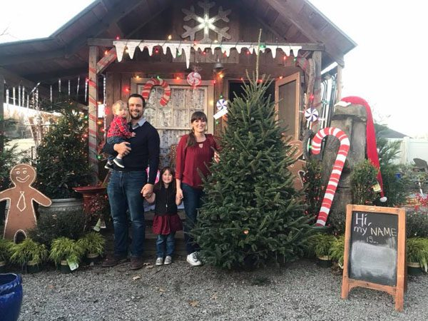 Family posing with their tree