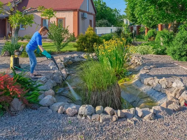 Woman cleaning her pond with a power washer